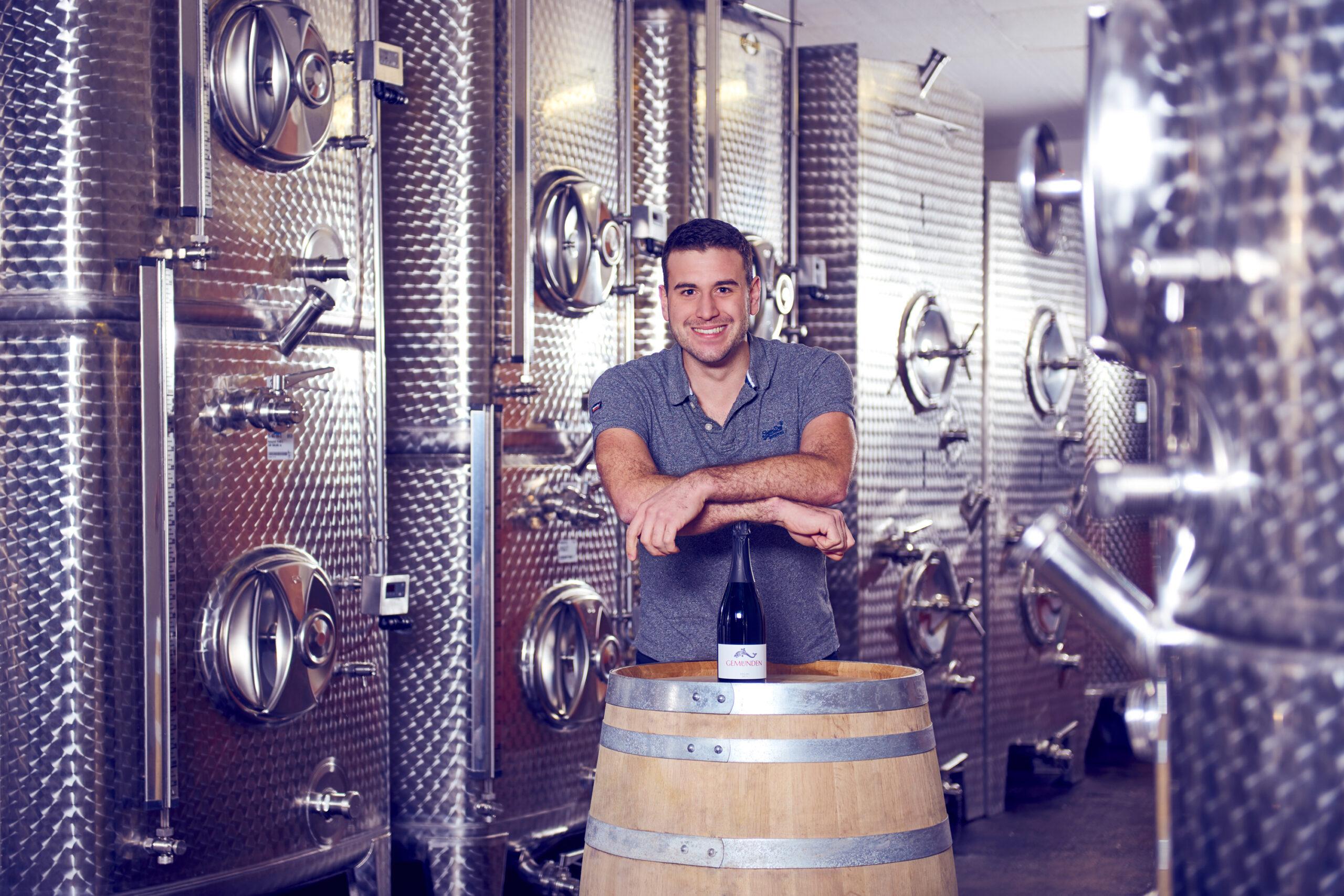 Jungwinzer Daniel Gemünden im heimischen Weinkeller vom Weingut Gemünden mit den Stahltanks im Hintergrund