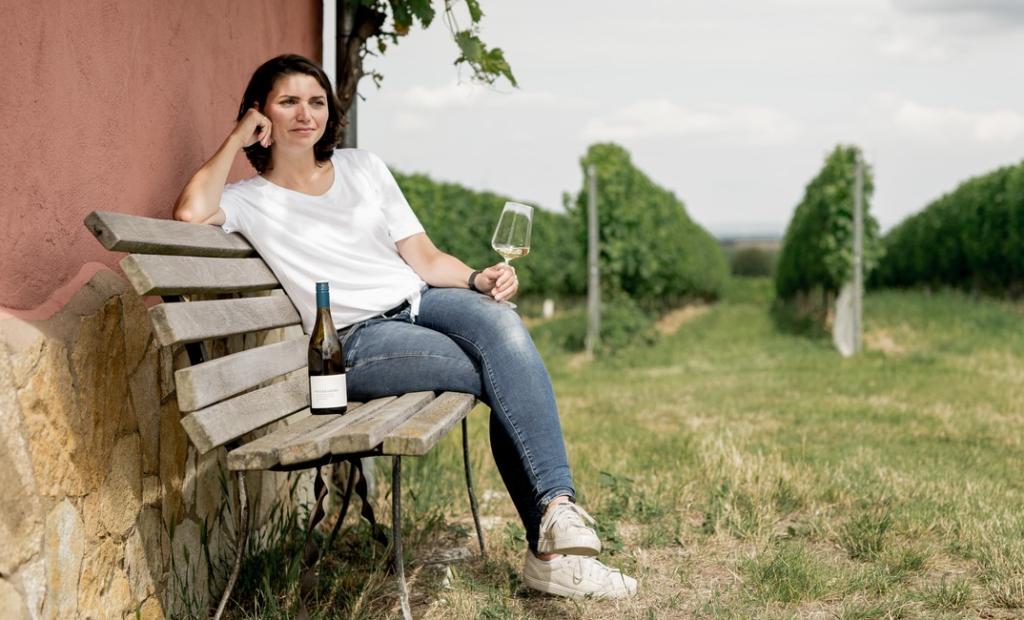 Gesine Roll vom Weingut Weedenborn sitzt mit ihrem Wein auf einer Bank